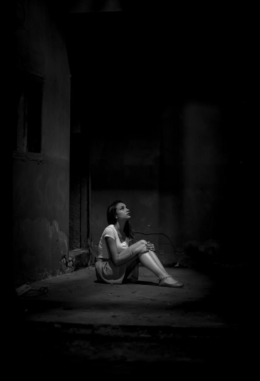 monochrome photo of woman sitting on floor