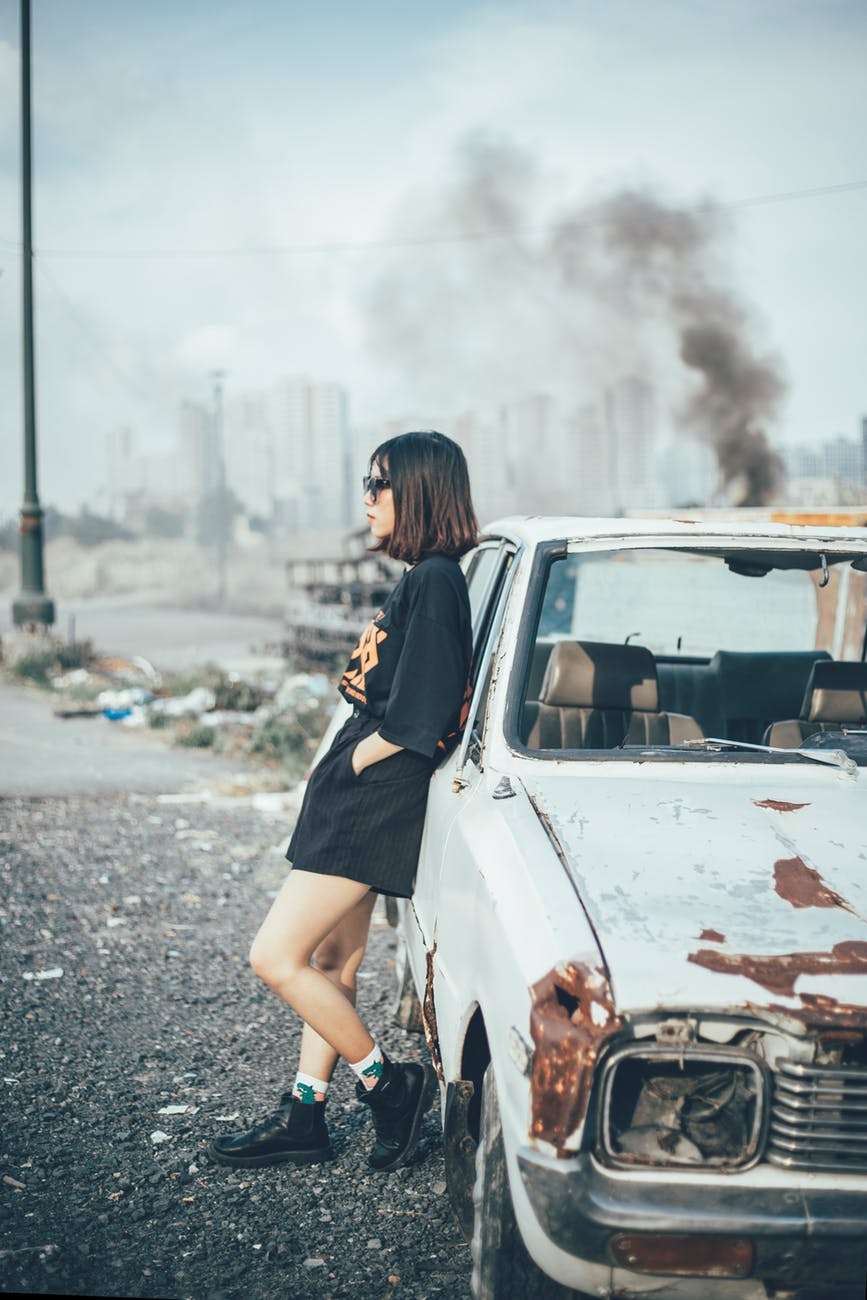 woman wearing black top leaning on white car