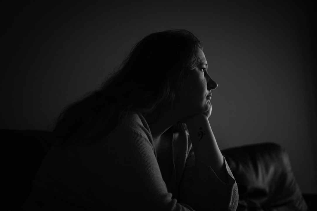 grayscale photography of woman sitting on sofa