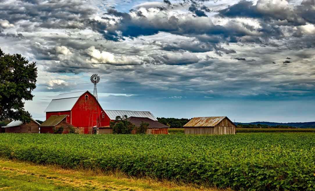 houses in farm against cloudy sky