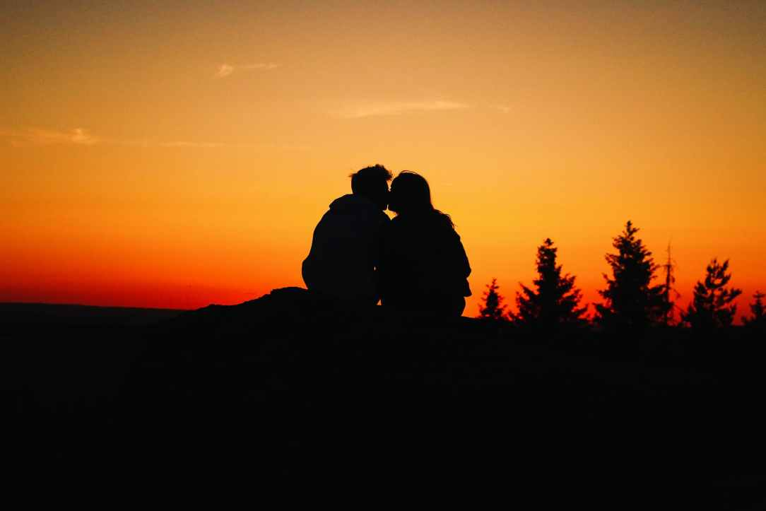 silhouette photo of couple kissing during golden hour