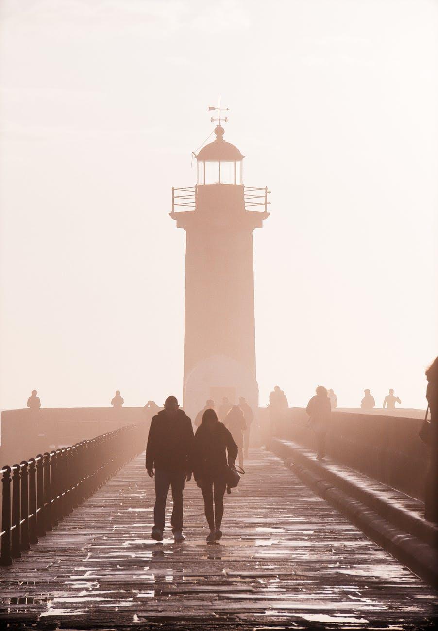 two people walking near lighthouse