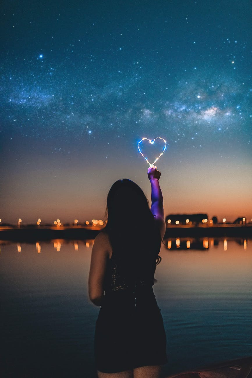 woman holding a heart shape light