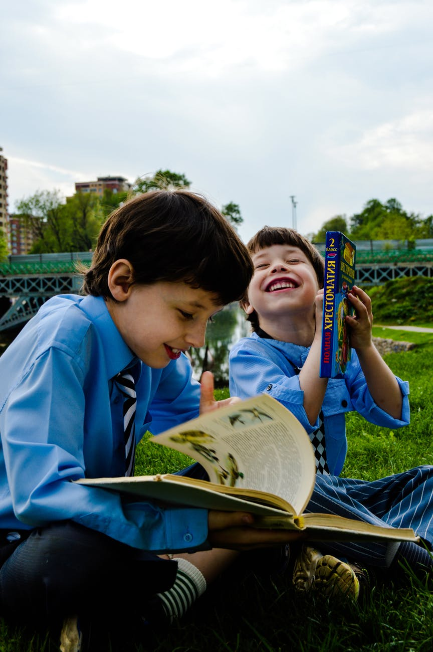 two boys seated on the grass laughing and reading books