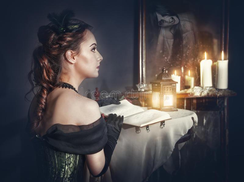 mulher-com-o-livro-no-vestido-retro-e-no-fantasma-no-espelho-66150944